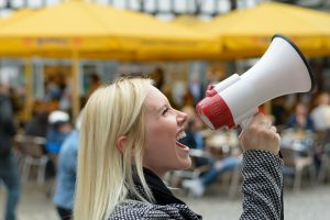 Woman yelling into a megaphone on an urban street voicing her displaeasure during a protest or demonstration, close up side view of her face