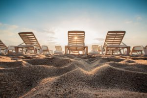 Beach chairs on the sands at sunrise, summer vacation getaways concept